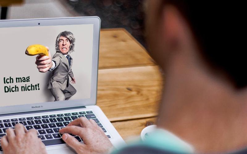 Mann sitzt vor geöffnetem Notebook