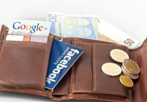 geöffnete Brieftasche mit Bargeld und Facebook- und Google Kärtchen